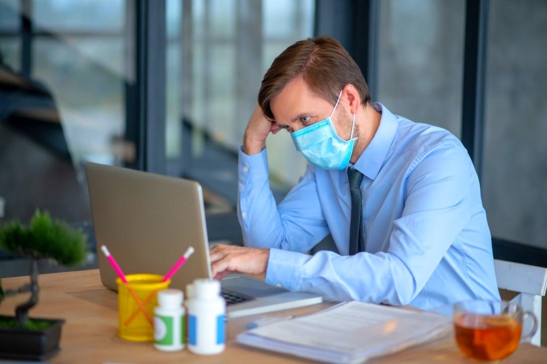 Employé de bureau muni d'un masque face au coronavirus