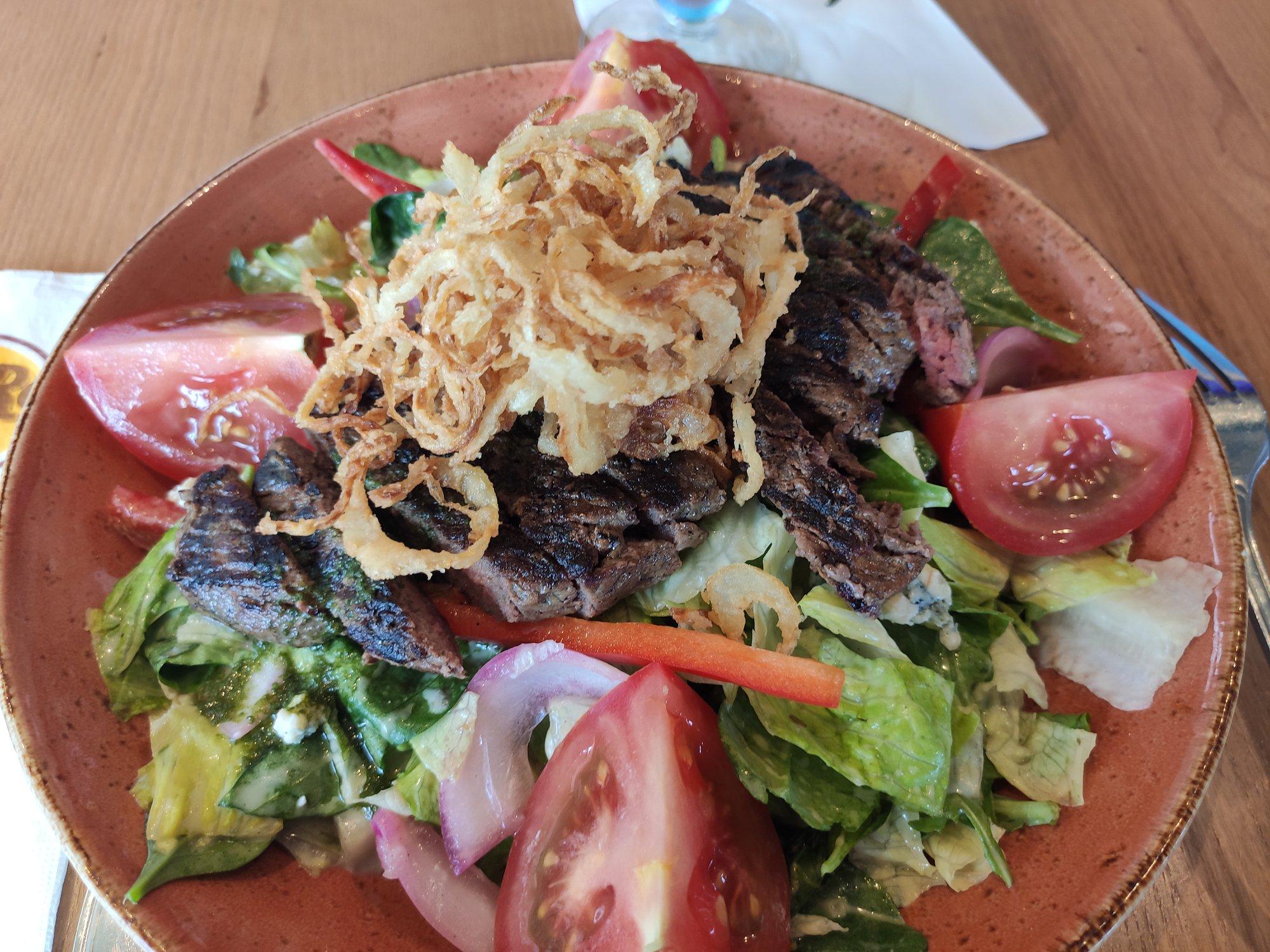Parmi les succès de la nouvelle carte, la steak salad, très réussie : tranches de bœuf grillées sur un lit de salades mélangées, vinaigrette au fromage bleu, oignons rouges croustillants, poivrons rouges, tomates , oignons grilles et d'éclats de fromage bleu