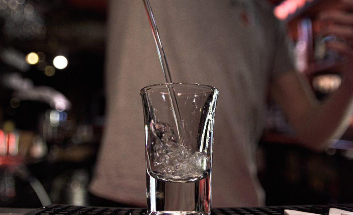 Shot de vodka servi par un bartender dans un bar de nuit